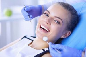 woman in a dentist chair and dentist holding tools, about splendid dental atascocita