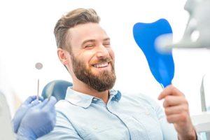 man smiling into hand mirror after periodontics atascocita tx